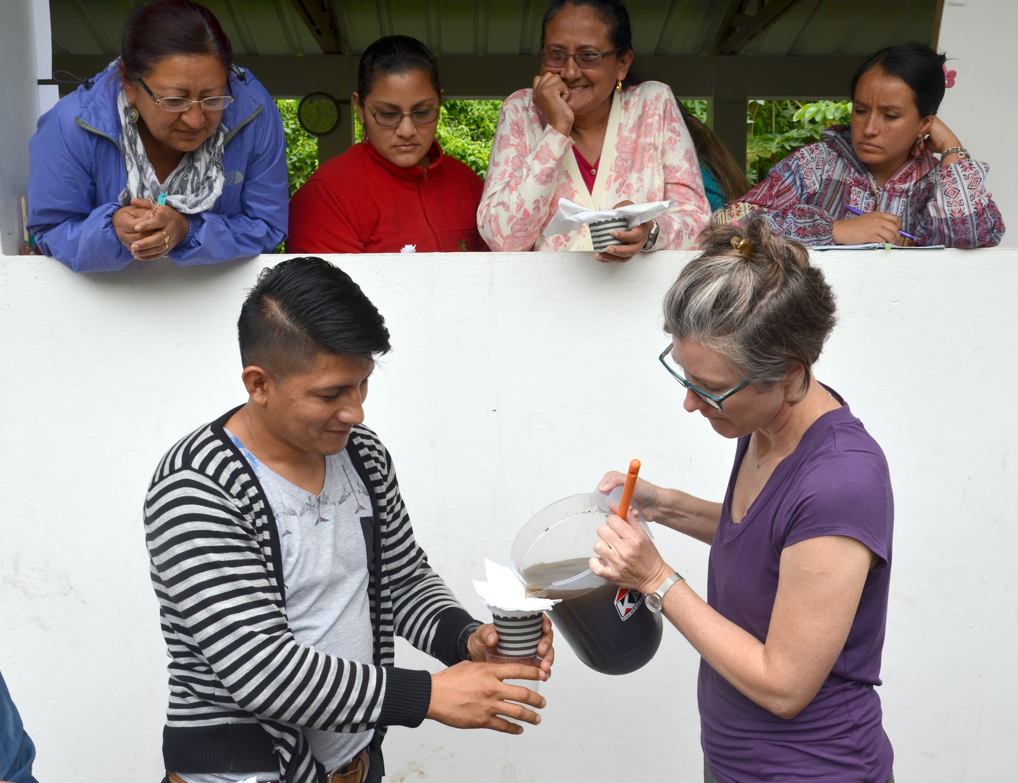 KC Busch works with teachers in the Galapagos Islands as they perform a water filtration experiment