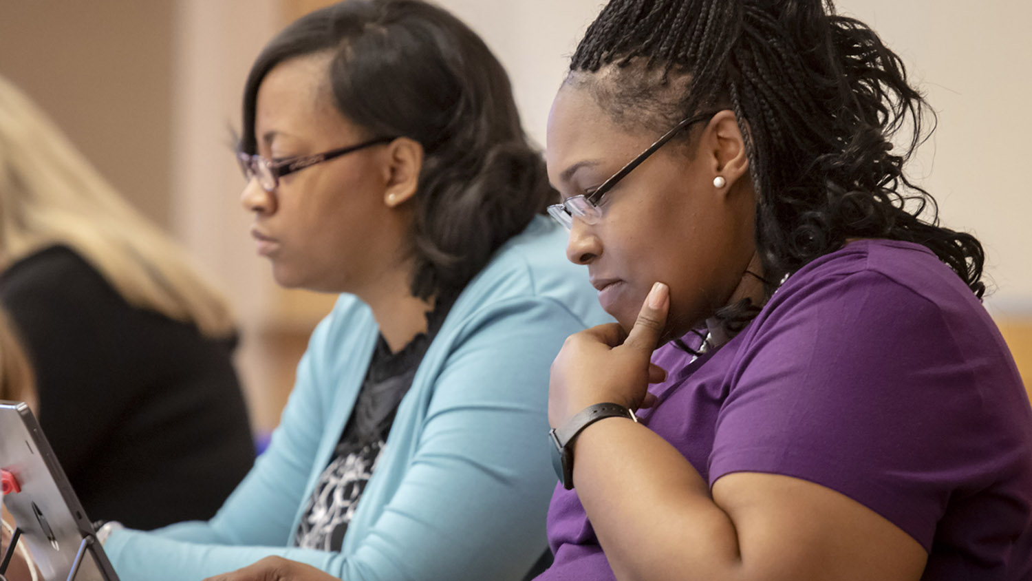 Two adult learners work side-by-side in a classroom