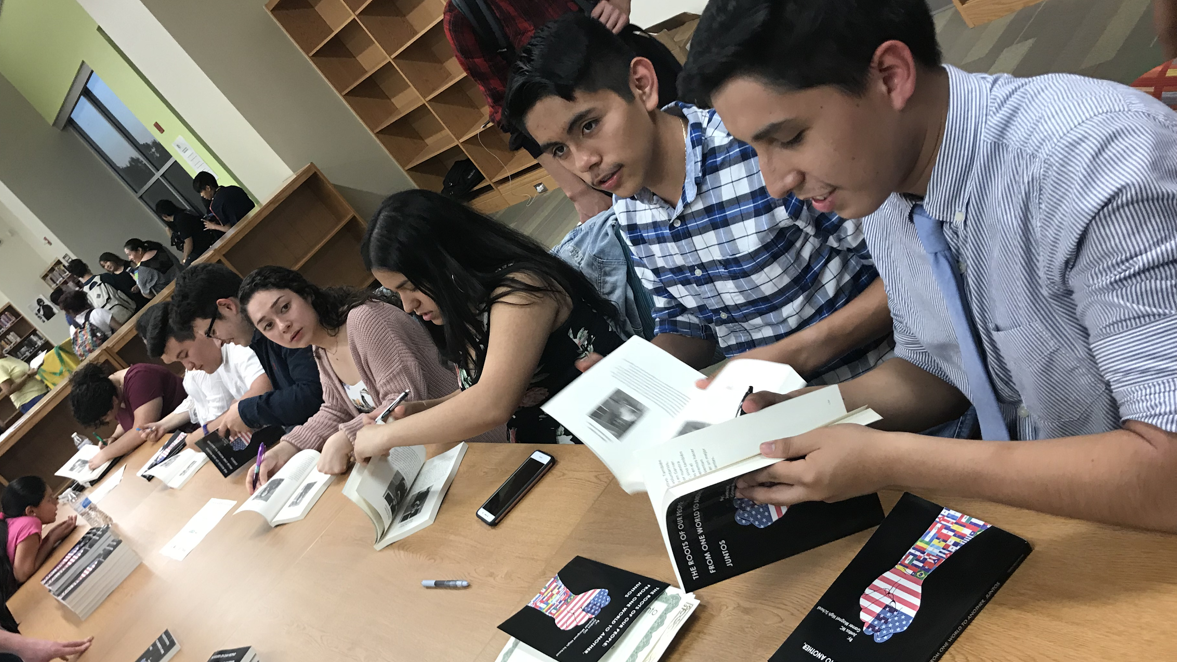 Photo of Juntos NC student authors signing copies of their recently published book.