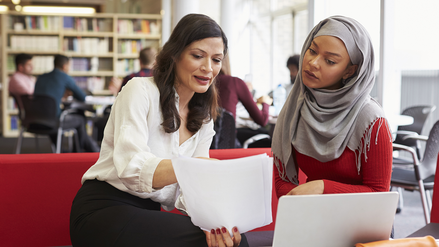 Photo of a faculty member reviewing documents with a female student