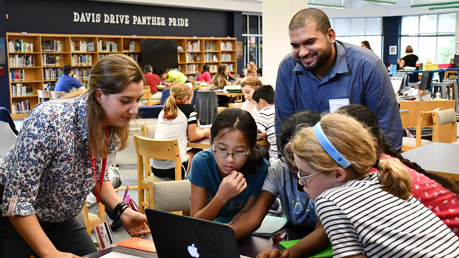 A photo of two NC State Education students mentoring a group of middle school students around a computer