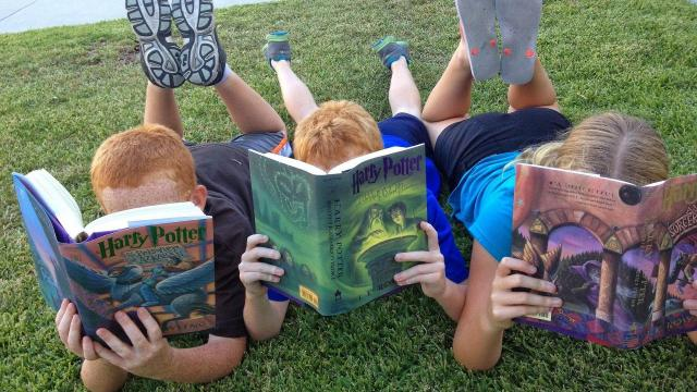 A photo of three children reading on a lawn