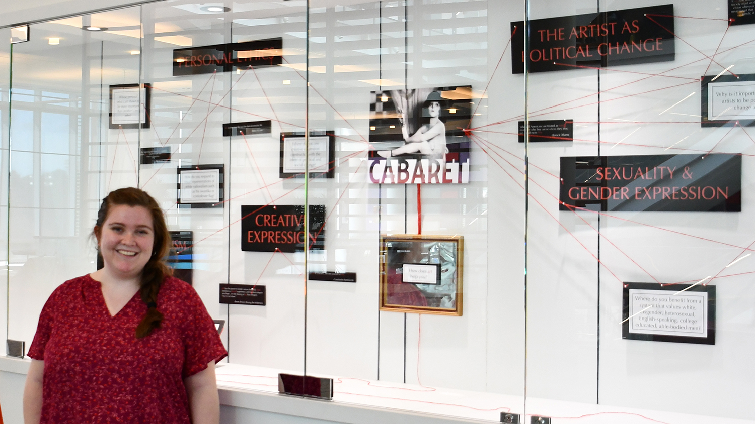 A photo of Erin Lisi by her Cabaret curriculum display
