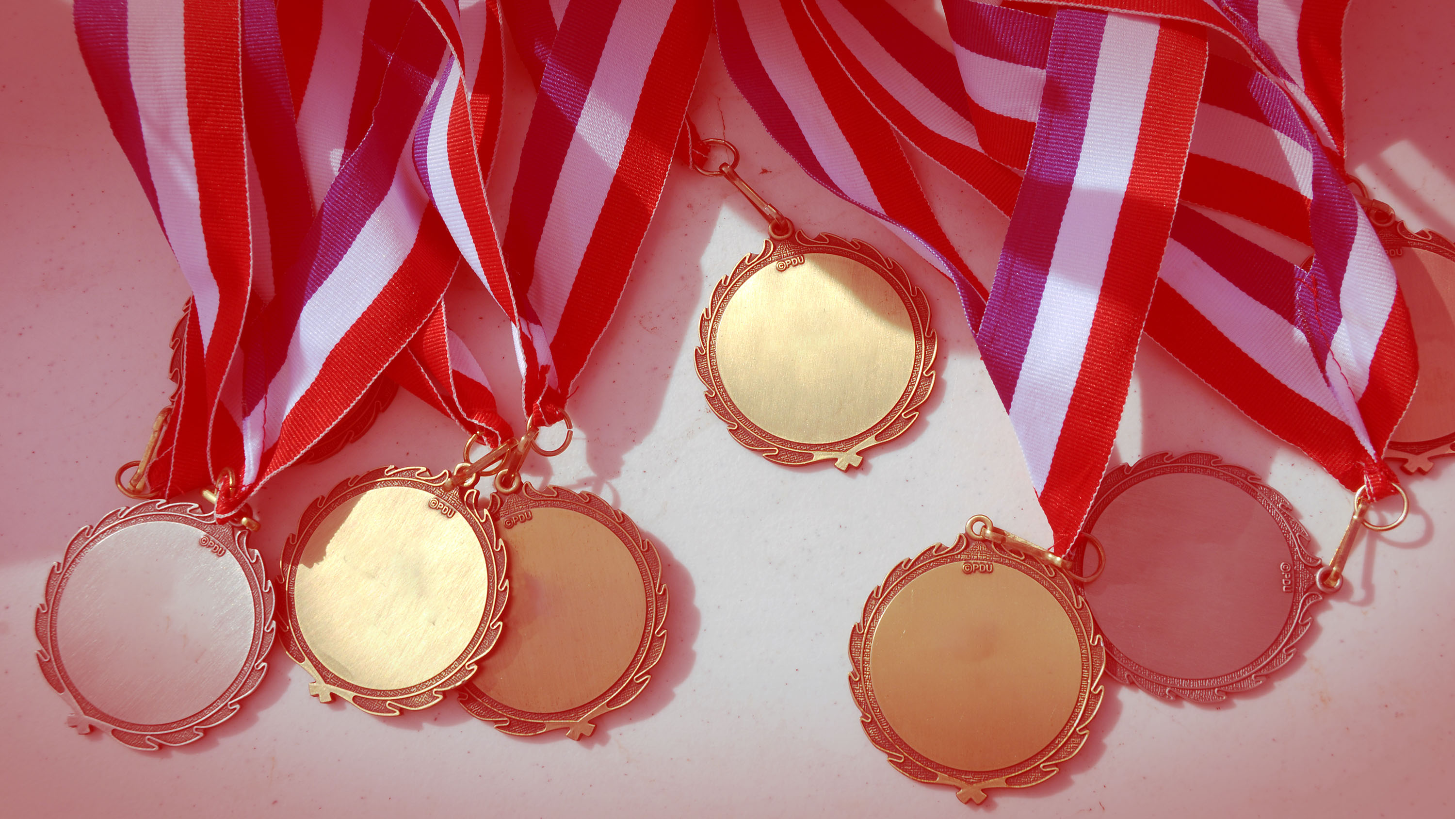 A photo of medals with a light red color overlay