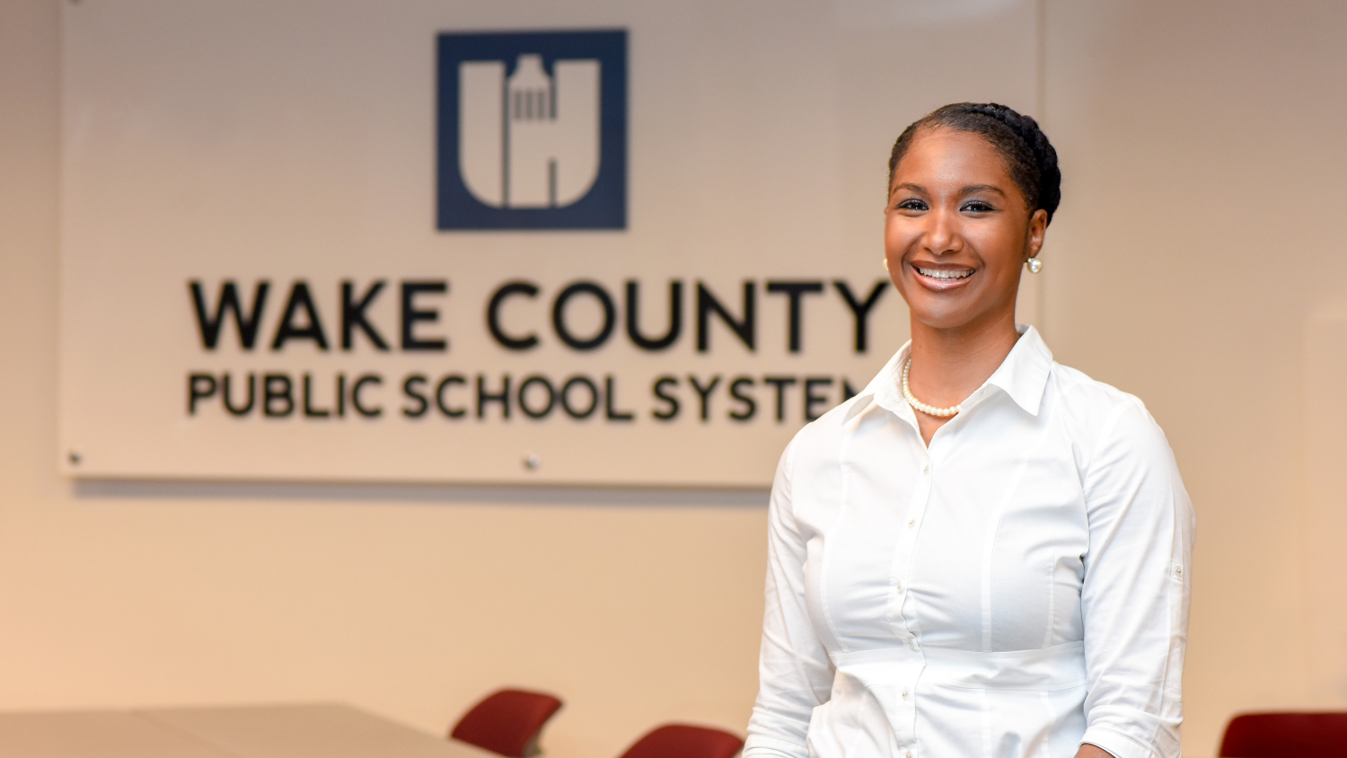 LaTeisha Jeannis in front of Wake County Public School System sign
