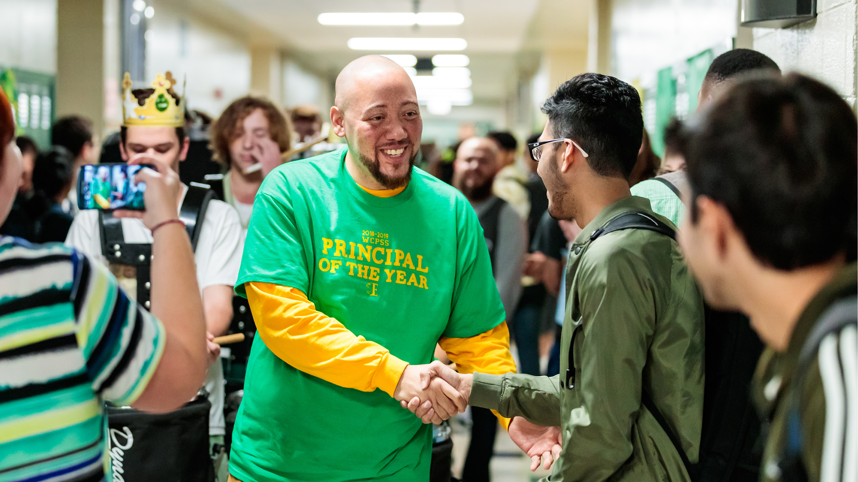 Will Chavis in school hallway shaking hands with students
