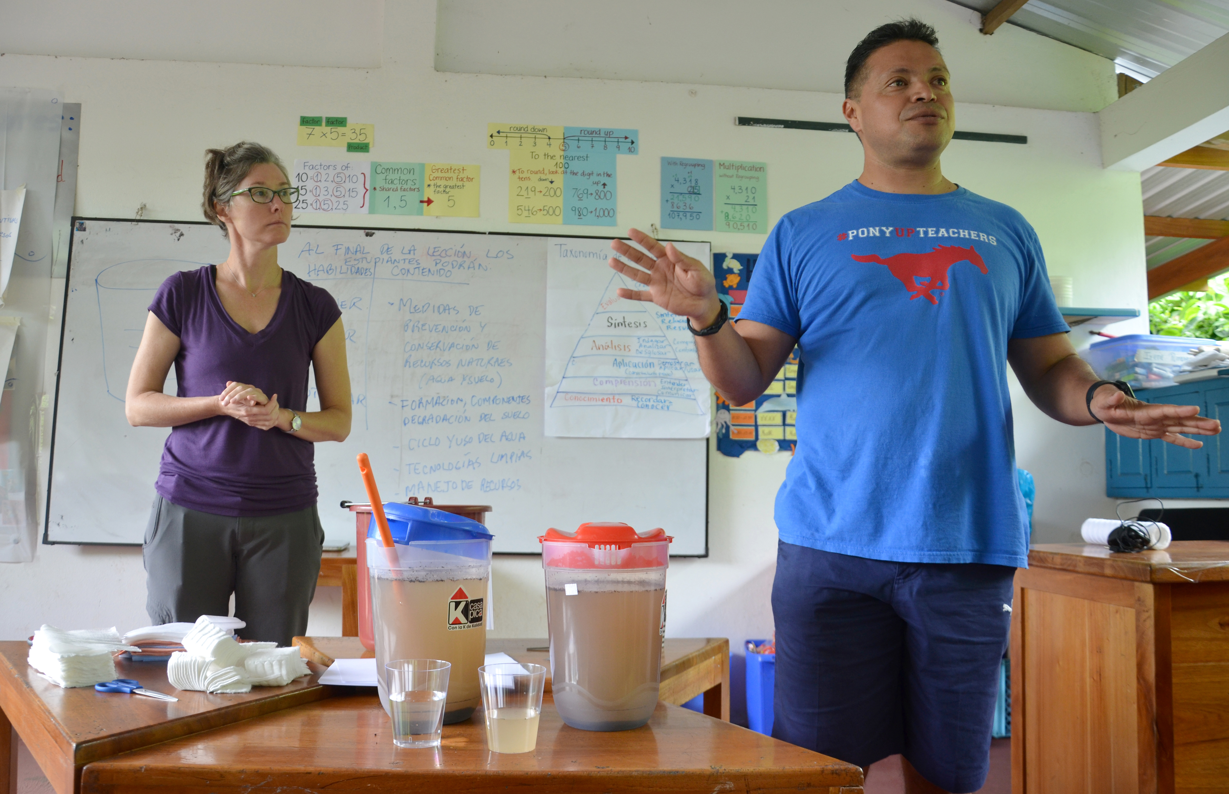 Assistant Professor KC Busch with a teacher as the perform a water filtration experiment in the Galapagos Islands