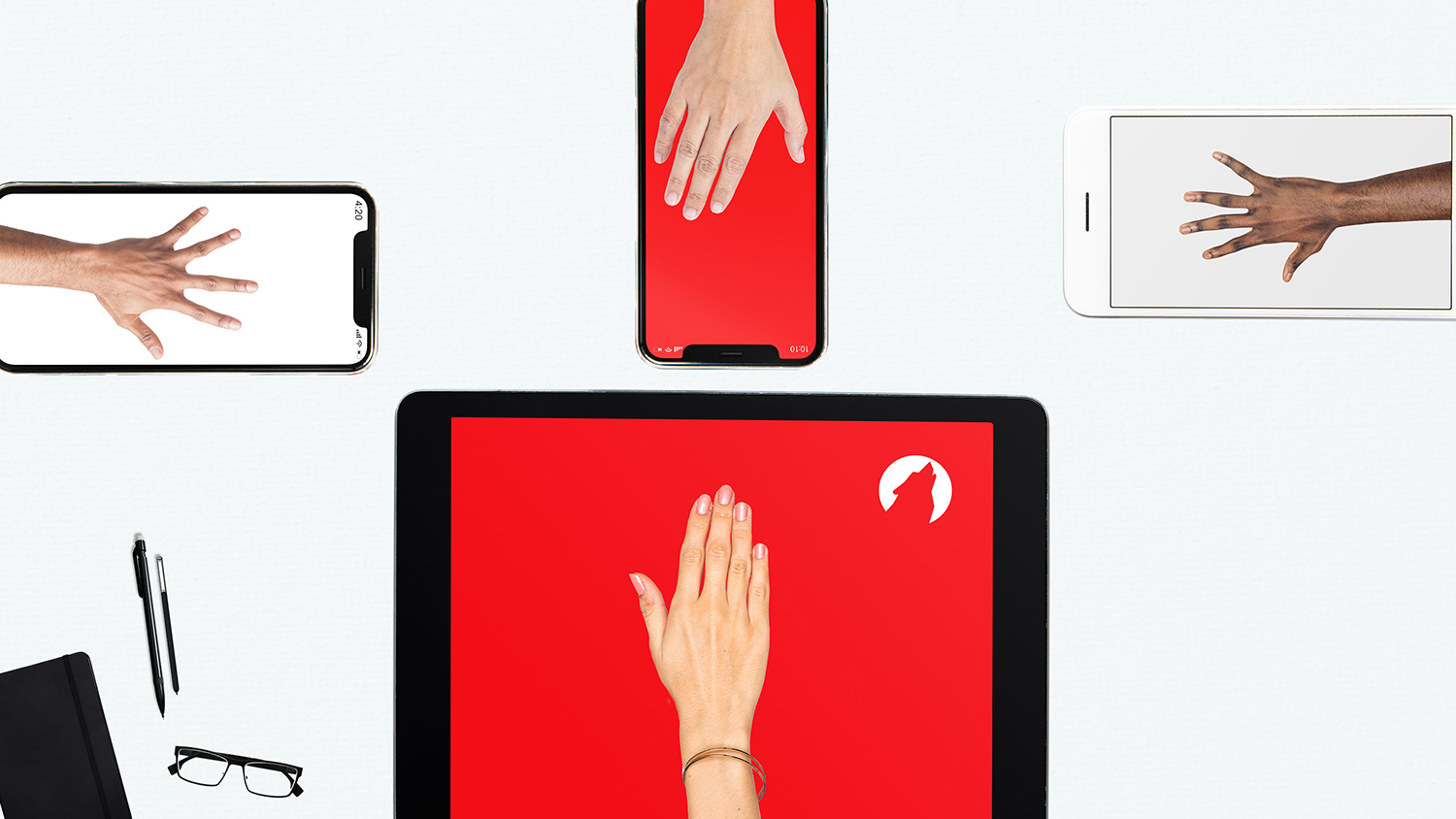 Four hands sitting on top of four separate electronic devices