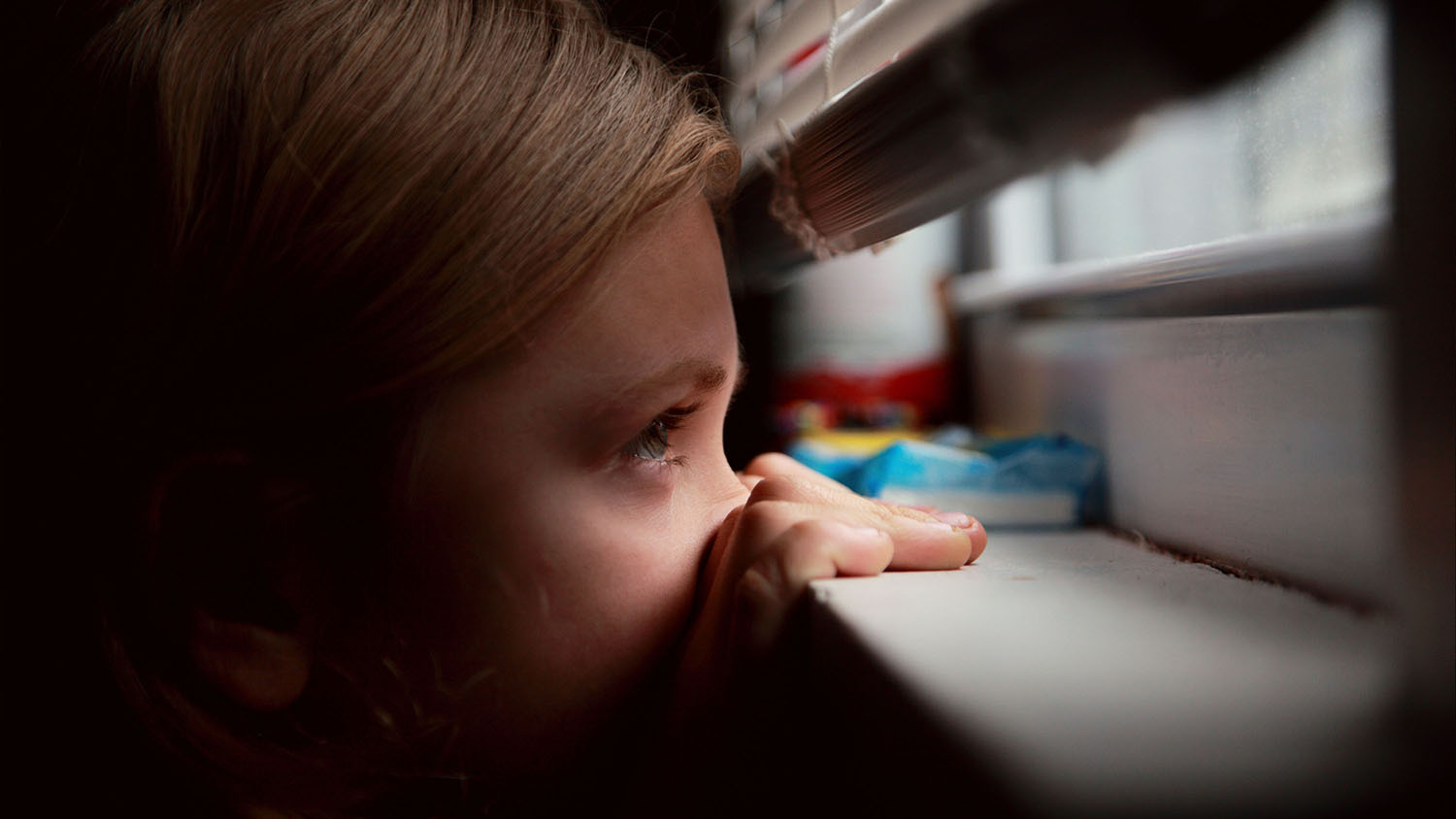 A young child peering through the bottom of a closed window