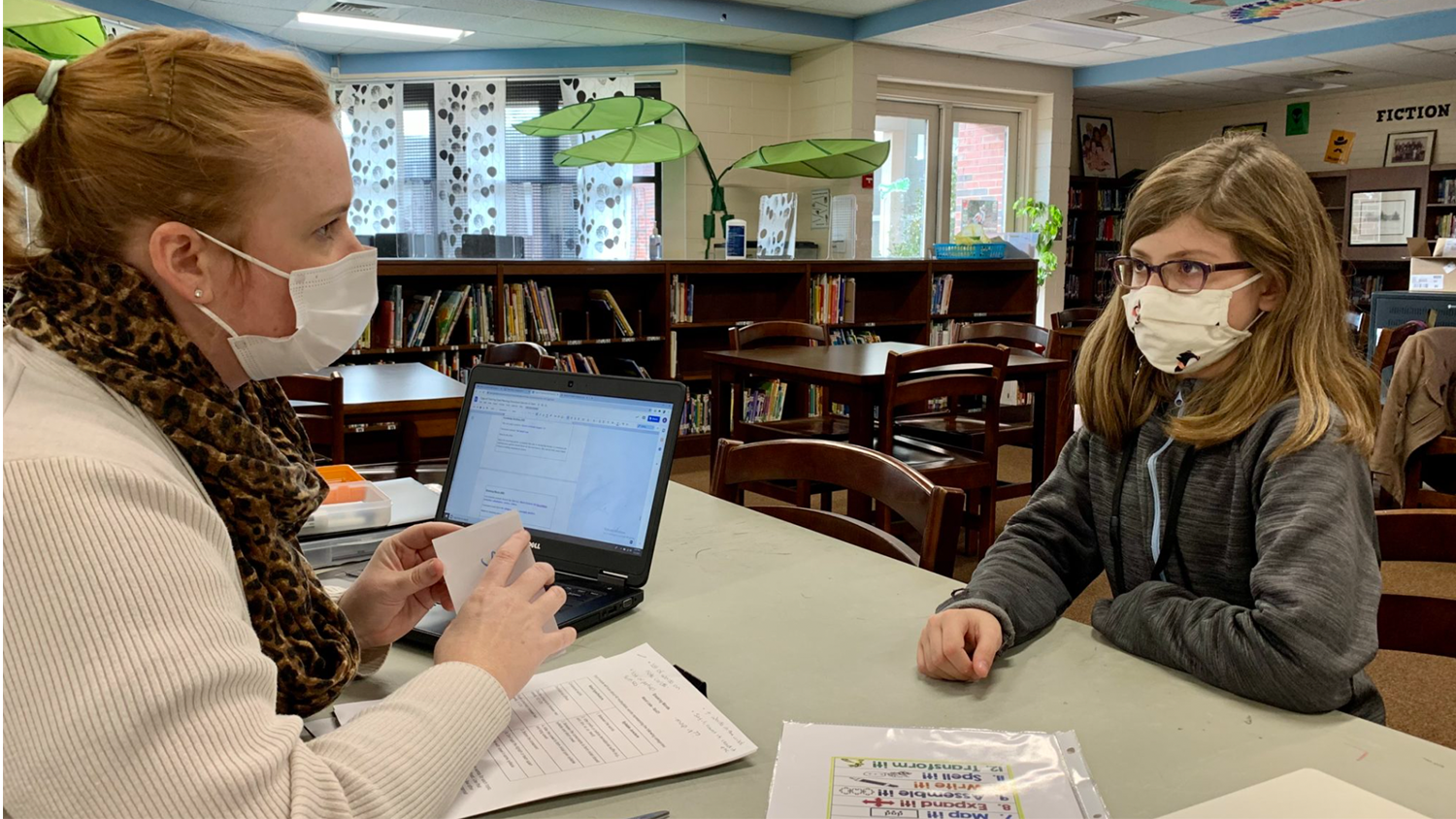 A student and teacher work together as part of the Yadkin Wolfpack Literacy Partnership
