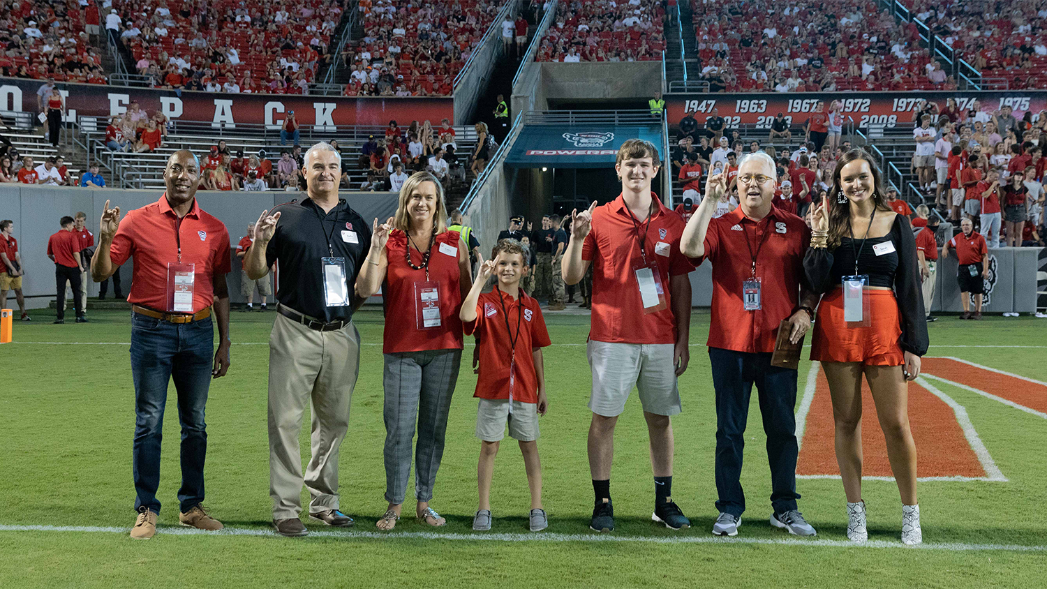 Sarah Daughtry and her family on the Carter-Finley Stadium field after being named NC State's Family of the Year