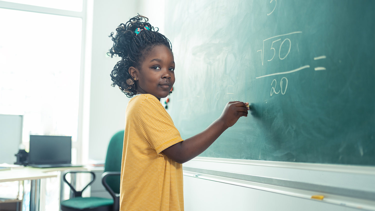 School girl thinking what to write on a blackboard.