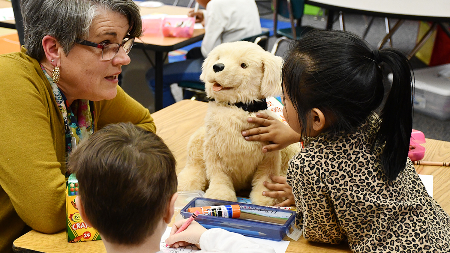 A teacher showing students a robotic dog