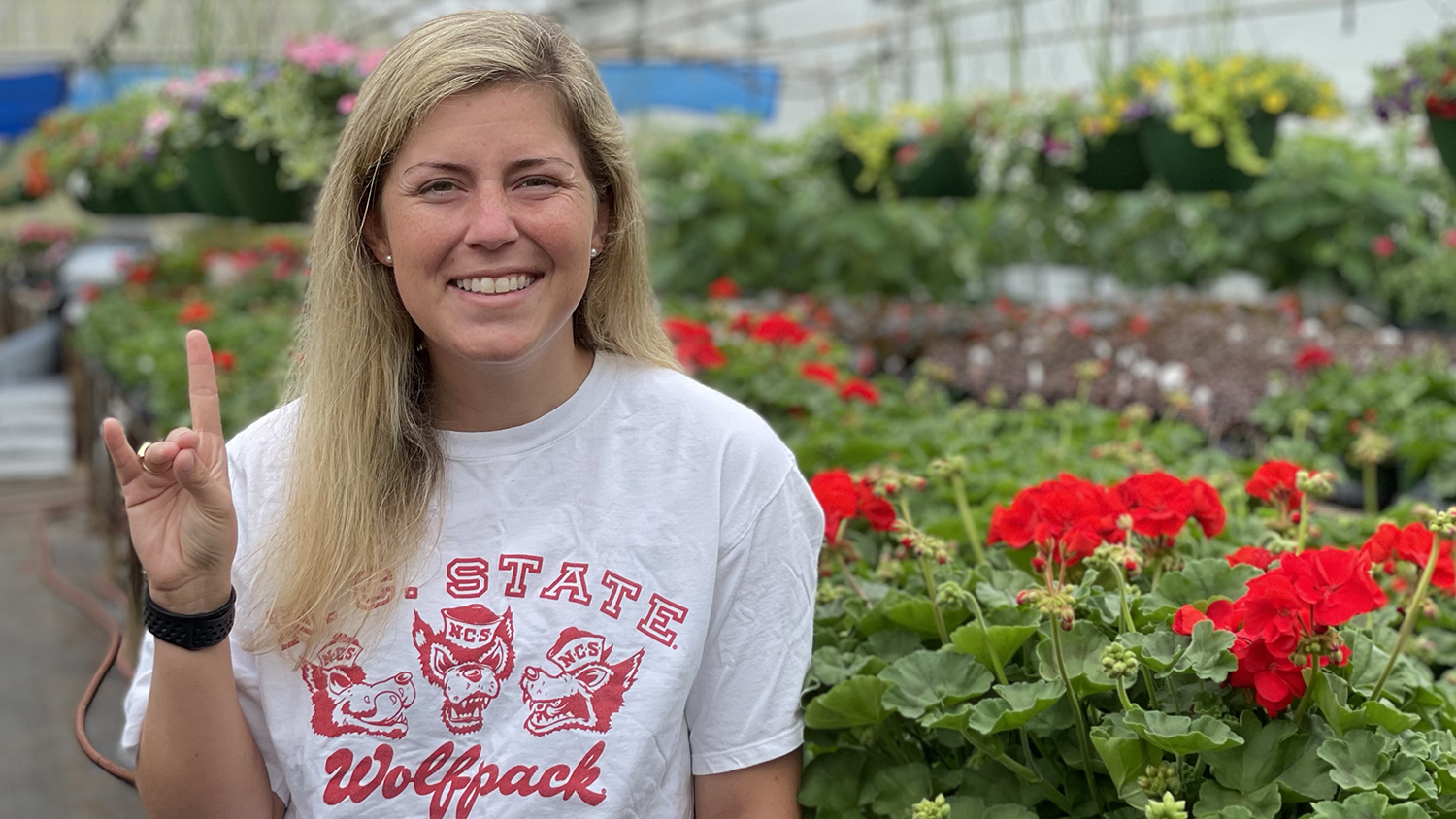 Ivy Briggs stands with the Wolfpack hand sign in a greenhouse full of flowers.