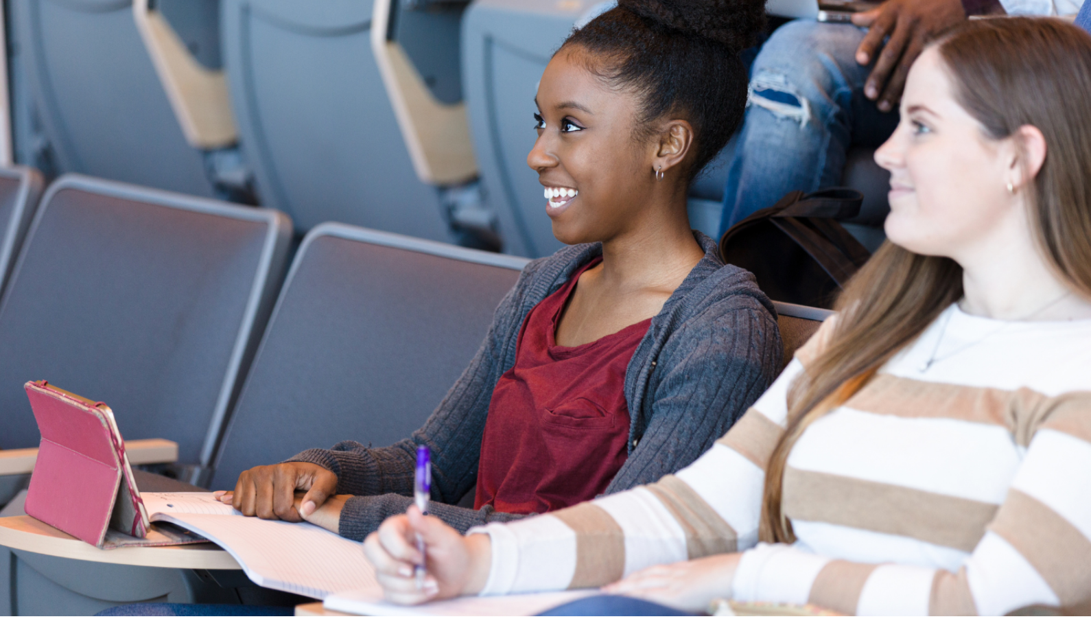 Two community college students sit side-by-side in a lecture hall