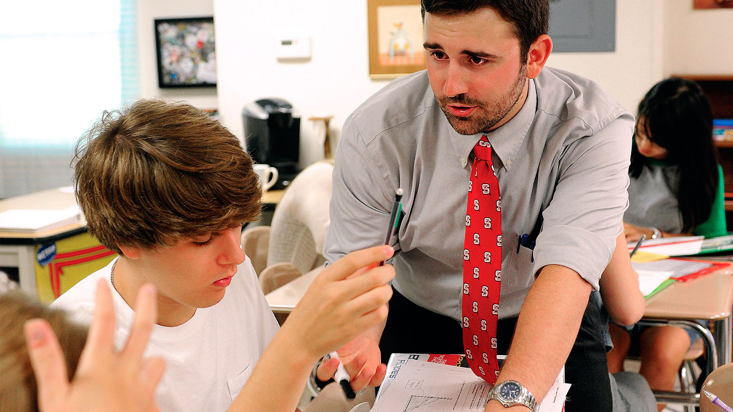 Teacher with student in classroom. Teacher is wearing an NCState themed tie.