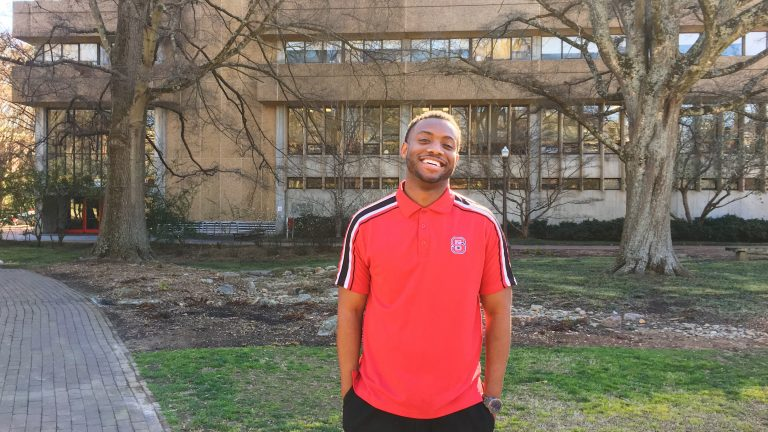 A College of Education graduate student in front of Poe Hall.