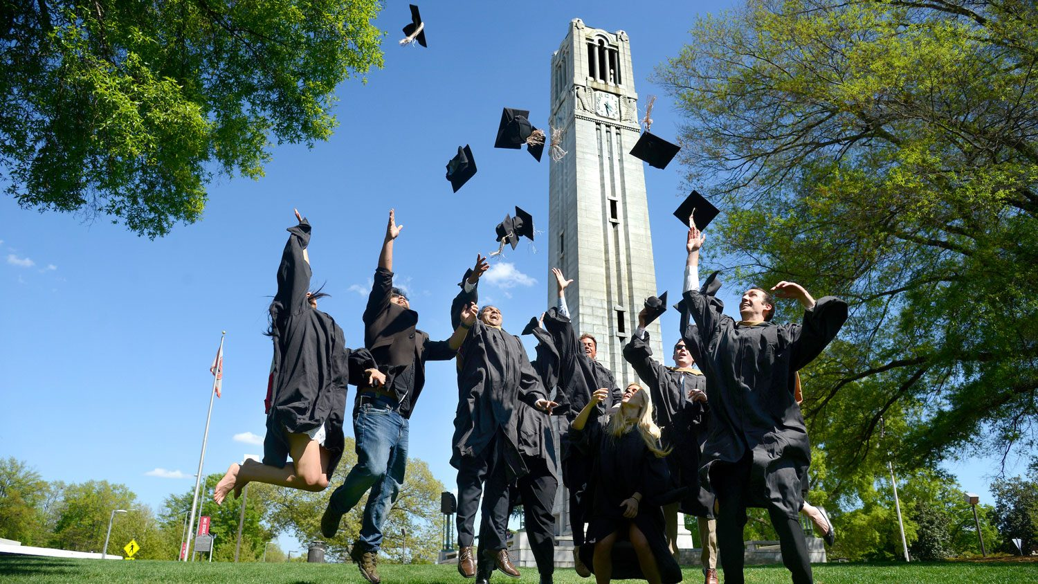 Graduating students in front of the Memorial Belltower.