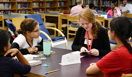 Three middle school students listen in as an NC State Education student guides a book discussion