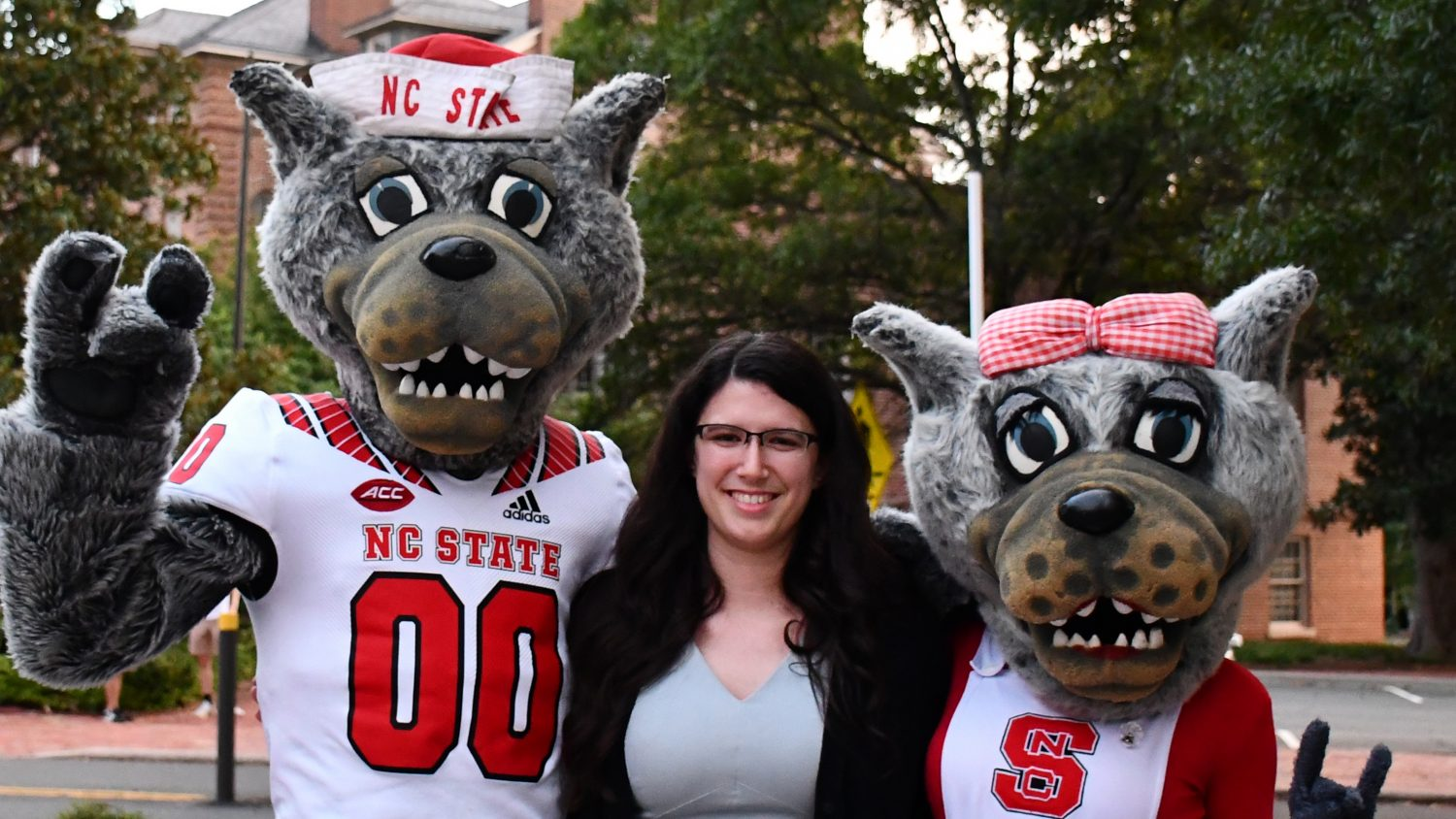 A photo of NC State Education graduate Ashley Lawson and Mr. and Ms. Wuf