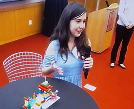 A photo of an elementary student presenting her Lego playground project.