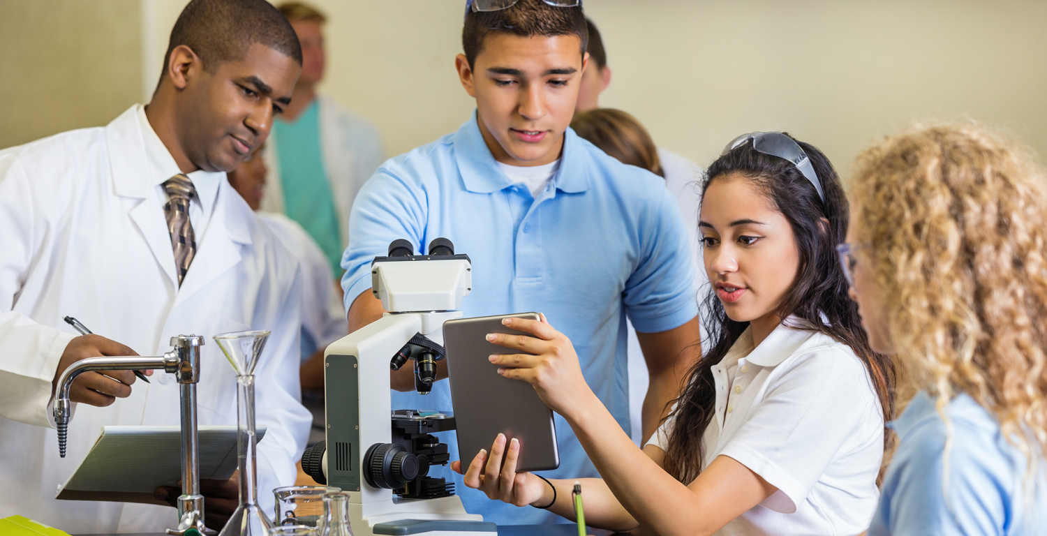 A group of students gather around a microscope.