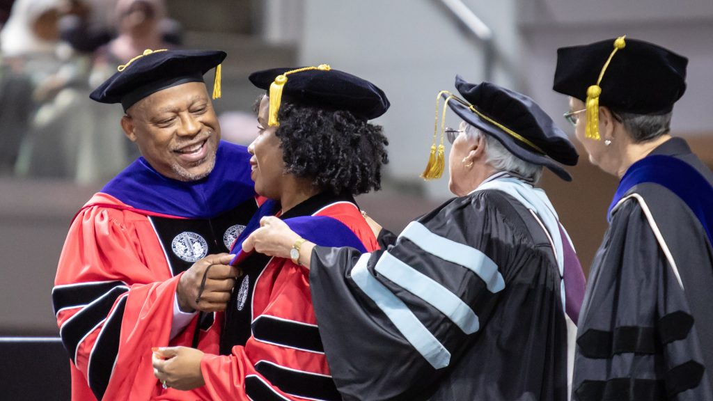 A photo of an NC State Education graduate being hooded at graduation