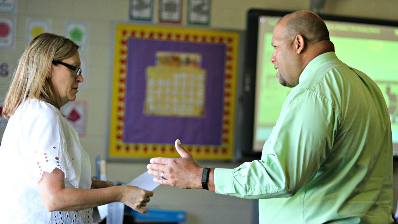 Two school leaders talk in a classroom