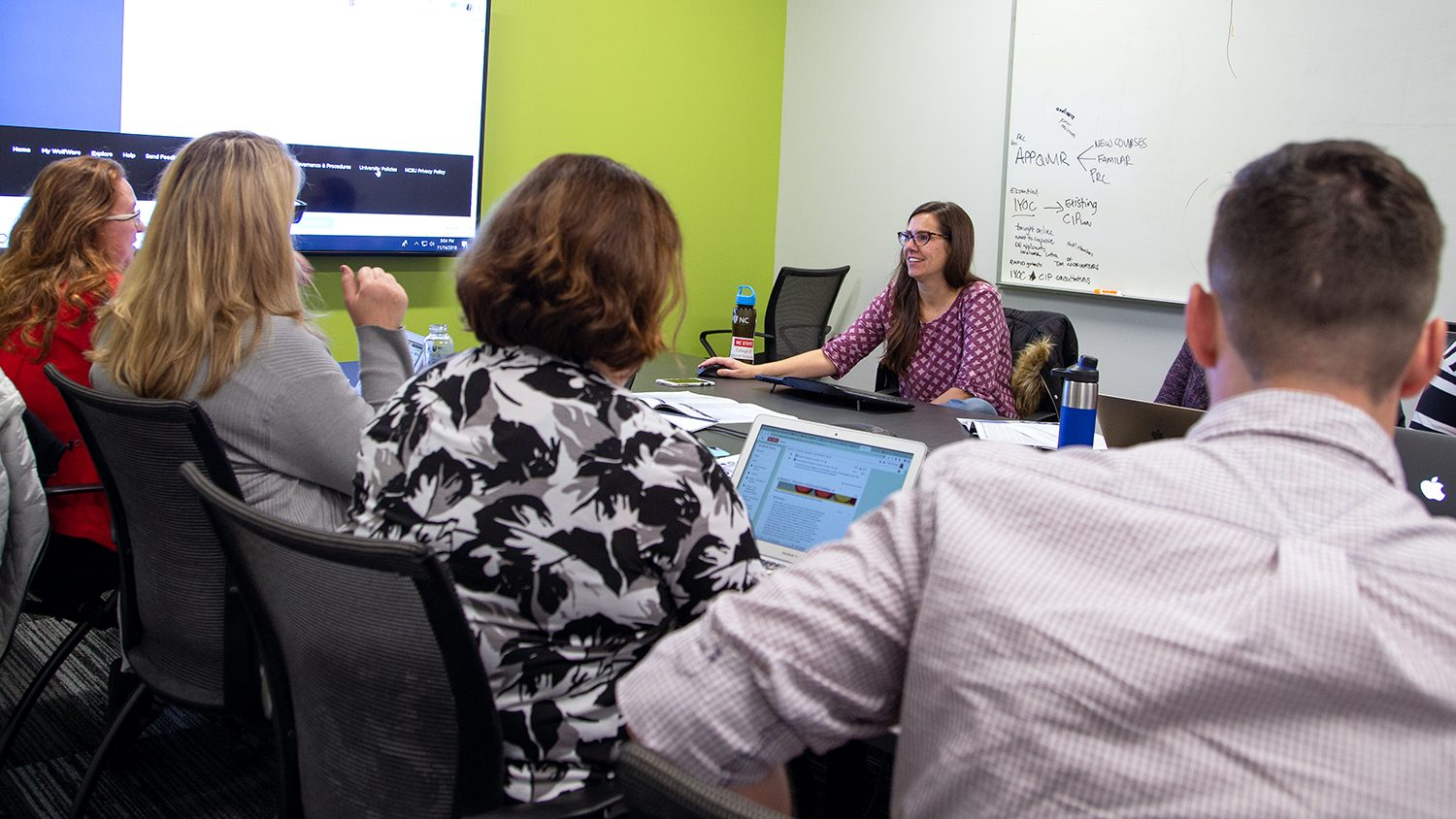 Instructional Designer Bethanne Tobey (center) facilitates a face-to-face working meeting of the Fall 2018 Online Course Improvement Program cohort. Bethanne is pictured at the back of the table with participants on the other side.