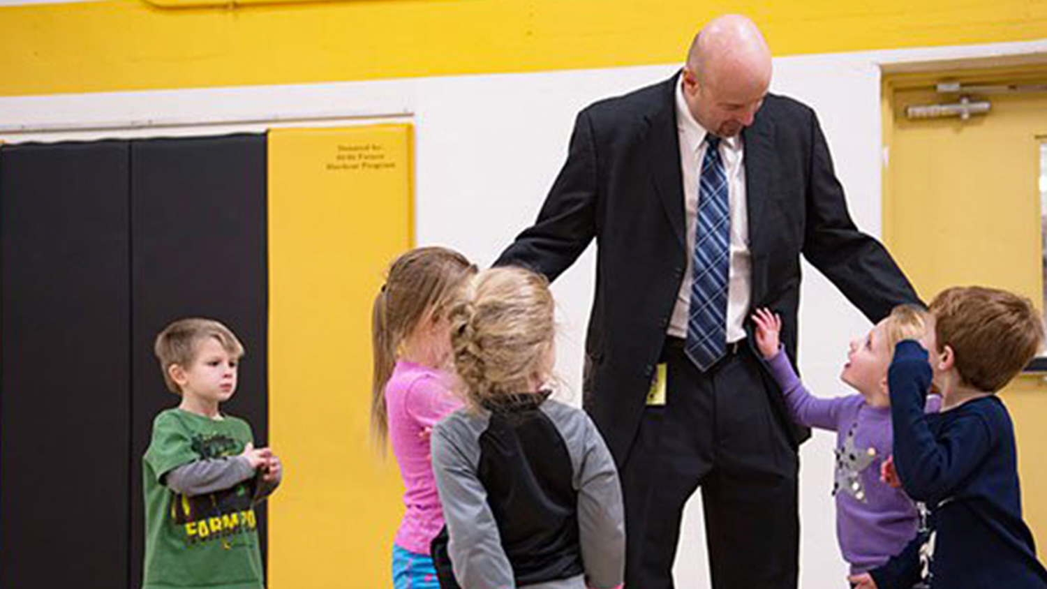 An elementary school principal with young students.