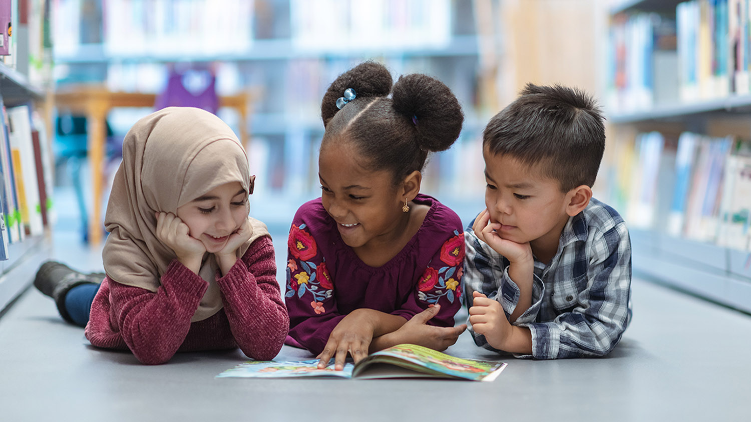 Three children lay on the floor to read together