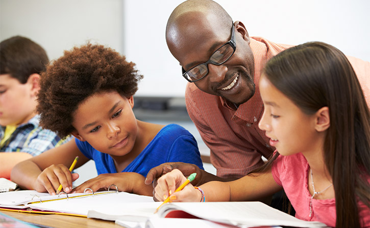 Teacher helping pupils study in the classroom
