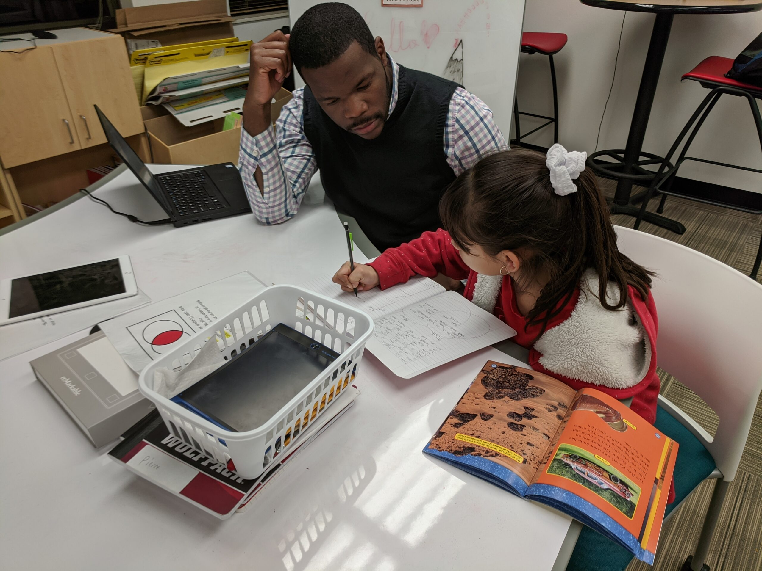 A teacher and student working at a desk